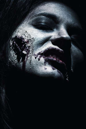 Close-up of a bloodthirsty zombi over black background. Stock Photo