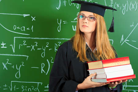 mba: Graduating student girl in an academic gown standing with books at the classroom.