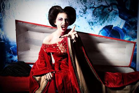 trumna: Krwiożerczy wampir kobieta wstaje z trumny na cmentarzu w nocy.