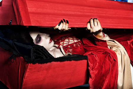 godforsaken: Bloodthirsty female vampire rises from the coffin on the night cemetery.
