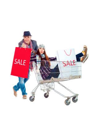 chicas de compras: Pareja alegre con un carrito de compras. Aislado sobre fondo blanco.