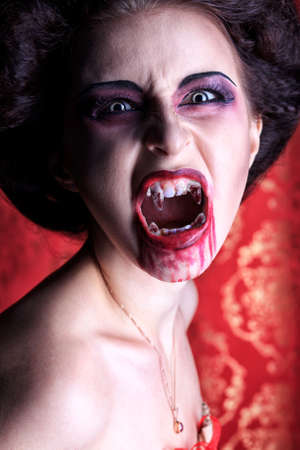 fangs: Portrait of a bloodthirsty female vampire. Stock Photo