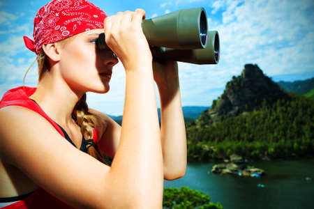 Young woman tourist is looking through the binoculars at the top of a mountain. photo