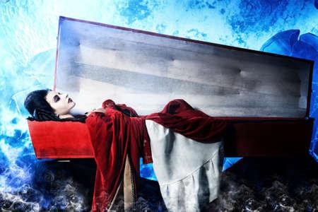 trumna: Kobieta wampir krwiożerczy leży w trumnie na cmentarzu w nocy.