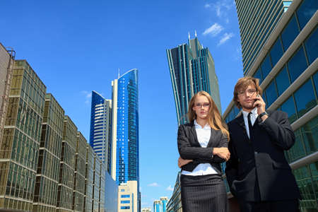 Business woman and business man is talking on mobile phone in front of skyscrapers.  photo