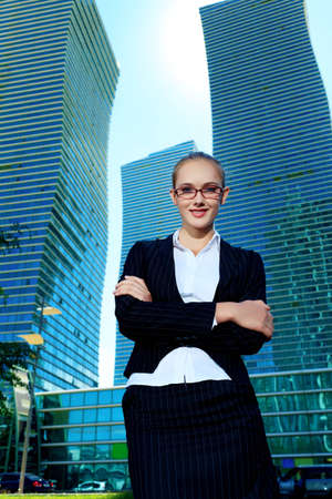 Smiling young business woman standing on the street of the big city. photo