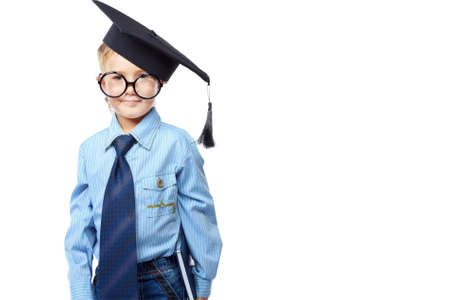 one little boy: Little boy in spectacles and academic hat standing over white background. Isolated. Stock Photo