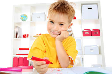 Little boy drawing in his notebook at home. Stock Photo - 15353701