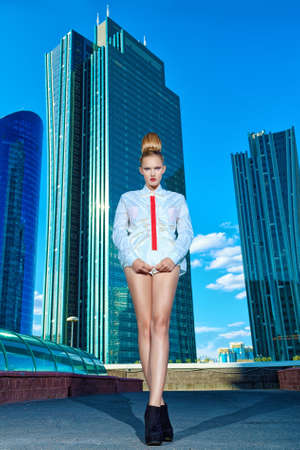 Full length portrait of a fashion model posing over big city background. photo