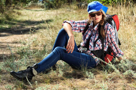 Beautiful girl tourist having a rest on a trekking trail. photo