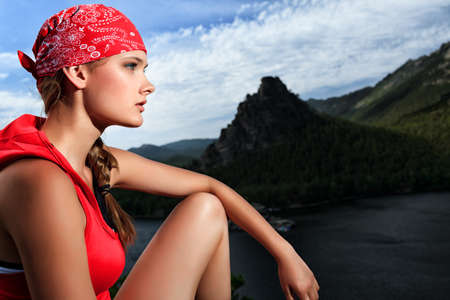 Young woman tourist is looking into the distance at the top of a mountain. photo