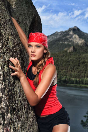 Beautiful woman alpinist is climbing on a mountain. photo