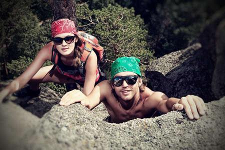 climbing: Pareja de j�venes alpinistas est�n subiendo en una monta�a.