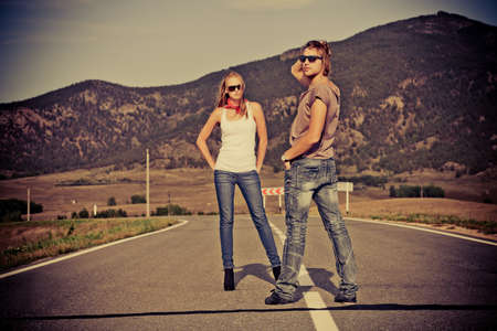 street fashion: Couple of modern young people posing on a road over picturesque landscape.