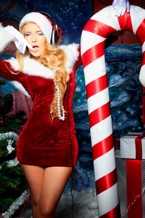 sexy christmas: Beautiful young woman in Santa Claus clothes and headphones over Christmas background. Stock Photo