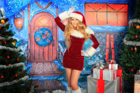 fur trees: Beautiful young woman in Santa Claus clothes over Christmas background.