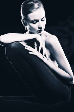 nude fashion model: Elegant young woman posing over black background. Light and shadow. Stock Photo