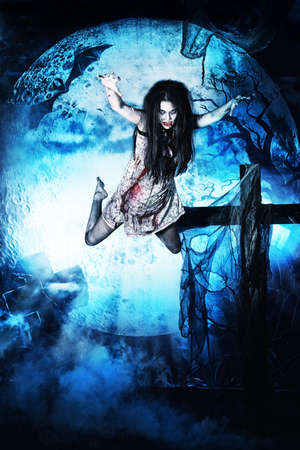 massacre: Bloodthirsty vampire flying at the night cemetery in the mist and moonlight. Stock Photo