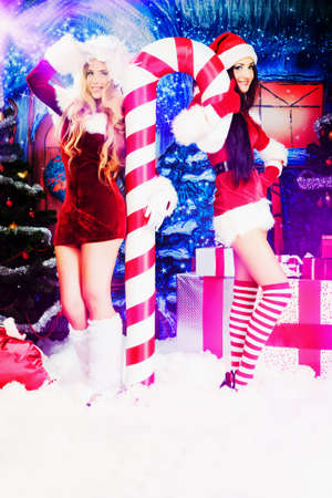 sexy costume: Two sexy young women in Christmas clothes posing over Christmas background.