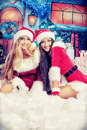 2 years: Two beautiful young women in Christmas clothes posing over Christmas background.