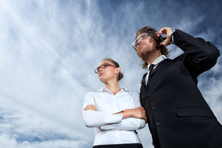 Successful business people  standing over blue sky and purposefully looking away. photo