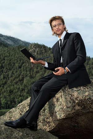 Successful business man working on a laptop on a peak of the mountain  photo