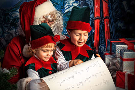 christmas costume: Santa Claus sitting with two little cute elves over Christmas background   Stock Photo