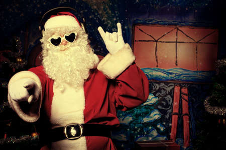 christmas costume: Santa Claus is listening to music in headphones  Christmas  Stock Photo