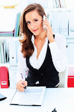 Modern business woman is talking on a cell phone at the office. Stock Photo - 15473585