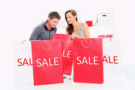 bag of money: Seasonal sale: happy couple holding shopping bags inside of a store.