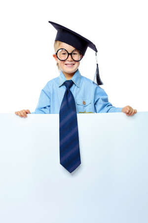 Portrait of a cute little boy in academic hat and big spectacles holding white board. Isolated over white background. photo