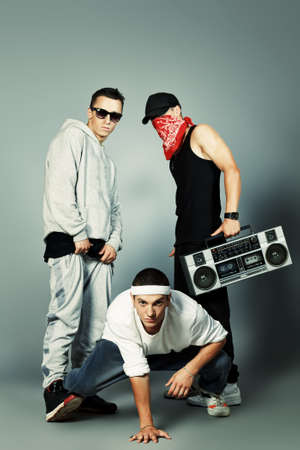 Group of trendy teenagers posing with boombox at studio. Stock Photo