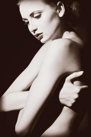 corps femme nue: Elégante jeune femme nue posant sur fond noir. Lumière et ombre.