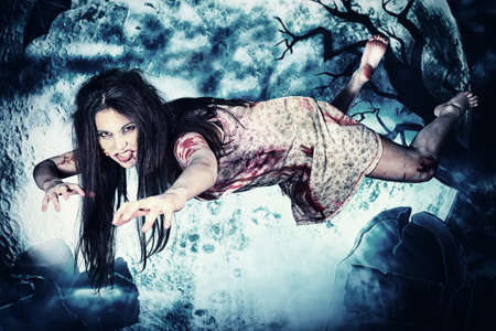 ghost woman: Bloodthirsty vampire flying at the night cemetery in the mist and moonlight. Stock Photo