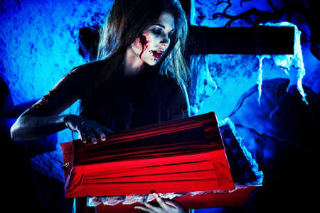 massacre: Bloodthirsty witch standing at the night cemetery and holding a coffin. Stock Photo