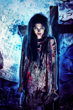 woman screaming: Bloodthirsty zombie standing at the night cemetery in the mist and moonlight. Stock Photo