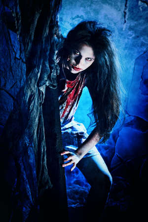 frightening: Bloodthirsty zombie standing at the night cemetery in the mist and moonlight. Stock Photo