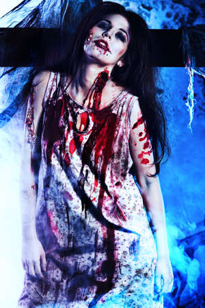 devil woman: Bloodthirsty zombie standing at the night cemetery in the mist and moonlight. Stock Photo