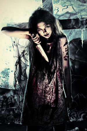 bloodthirsty: Bloodthirsty zombie with a knife standing at the night cemetery in the mist and moonlight.