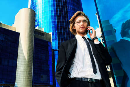 Young businessman talking on his mobile phone in the big city. photo