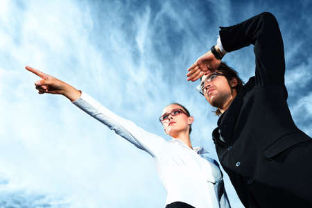 purpose: Successful business people  standing over blue sky and purposefully looking away. Stock Photo