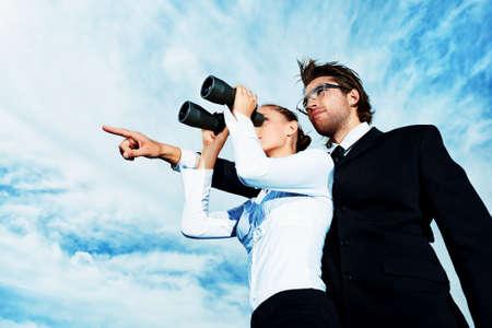 Succesvolle zakenmensen zich over blauwe hemel en doelgericht wegkijken. Stockfoto