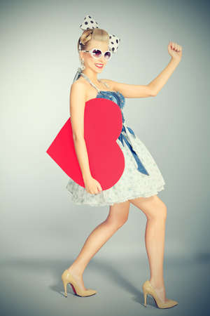 Beautiful young woman with pin-up make-up and hairstyle posing in studio with red heart. photo