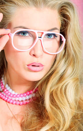 temptative: Portrait of a charming blonde woman in pink spectacles posing in studio over pink background. Stock Photo