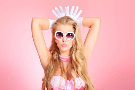 temptative: Portrait of a charming blonde woman posing in studio over pink background.