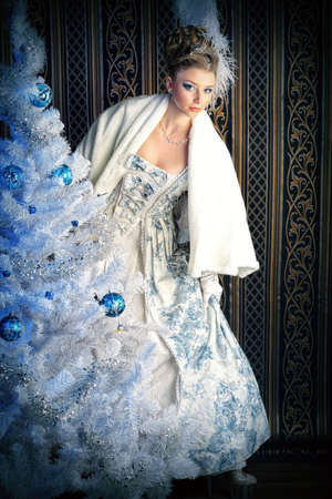 Portrait of the elegant woman posing with Christmas tree over vintage background.  photo