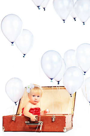 Little girl is sitting in the old suitcase under many balloons. Isolated over white. Stock Photo - 15821690
