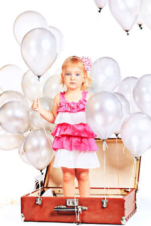 Little girl in the old suitcase under many balloons. Isolated over white. Stock Photo - 15821692