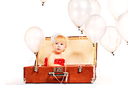 Little girl is sitting in the old suitcase under many balloons. Isolated over white. Stock Photo - 15608387