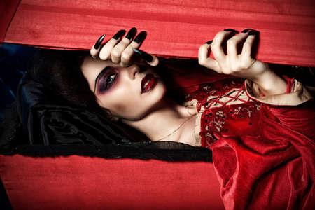 Vampiro assetato di sangue femminile sorge dalla bara nel cimitero notte.